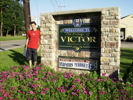 Victor in front of sign welcoming travelers to the Village of Victor, New York.