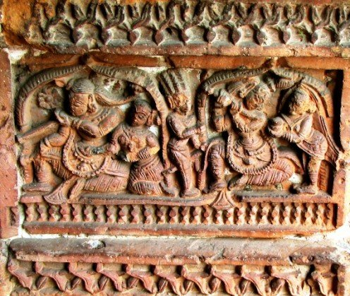 Krsna plays flute  with the expectation of meeting Radha while  messenger-woman comes and whispers that Radha is angry and upset. 17th century terra cotta temple,Bansberia,West Bengal.