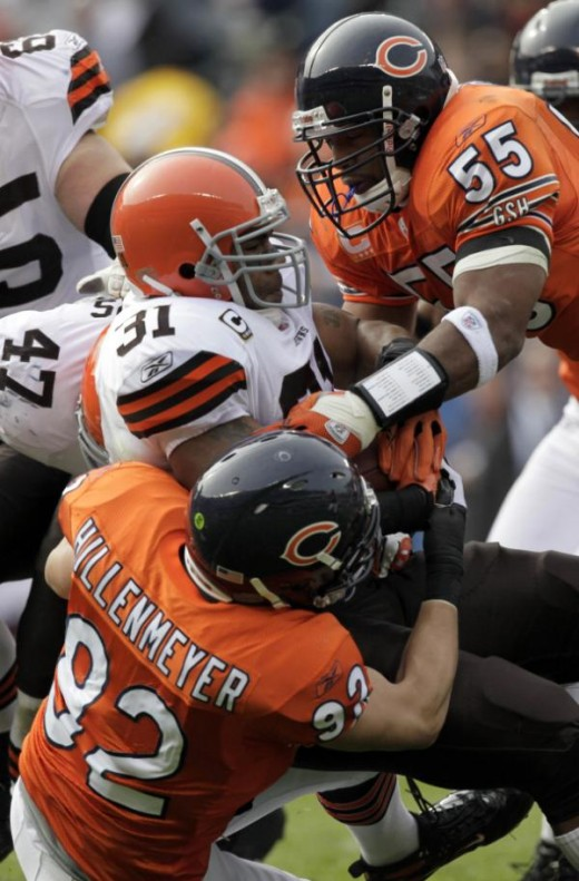 Cleveland Browns running back Jamal Lewis (31) is tackled by Chicago Bears linebackers Hunter Hillenmeyer (92) and Lance Briggs (55) in the first quarter of an NFL football game in Chicago, 11/01/09 (AP Photo/Kiichiro Sato)