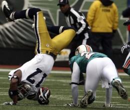 New York Jets wide receiver Braylon Edwards (17) flips over Miami Dolphins cornerback Sean Smith (24) while carrying the ball during the first quarter of an NFL football game at Giants Stadium in East Rutherford, N.J., Sunday, Nov. 1, 2009. (AP Photo