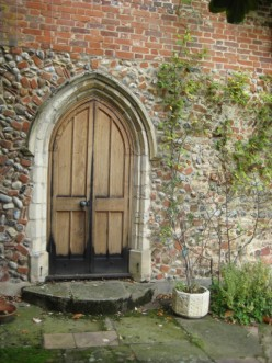 photo - an arched doorway set into a flint and brick wall.