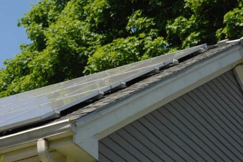 Solar panels lie close to the roof on mounts, which are installed by drilling holes through to the rafters. Consider putting a new roof on before installing solar panels so you don't have to remove the panels so soon for another roof replacement.