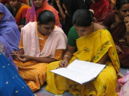 Microfinance loan clients in India check their books.