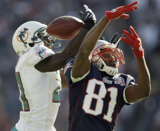 Miami Dolphins cornerback Vontae Davis, left, goes up over New England Patriots wide receiver Randy Moss (81) to intercept a Tom Brady pass during the first quarter of their NFL football game in Foxborough, Mass., Sunday, Nov. 8, 2009. (AP Photo/Char