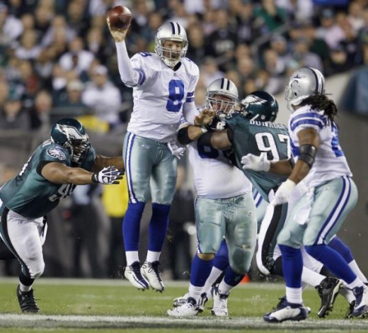 Tony Romo, center, passes to running back Marion Barber, right, as Philadelphia Eagles defensive tackle Mike Patterson, left, reaches for Romo during the first half of an NFL football game Sunday, Nov. 8, 2009, in Philadelphia. (AP Photo/Matt Slocum)