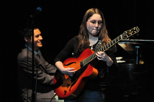 This concert photo shows the good of going manual in settings. The program mode would have washed out the young guitarist's face. Choice of a large fstop allowed for enough light and put the pianist in slightly soft focus keeping the guitarist as the