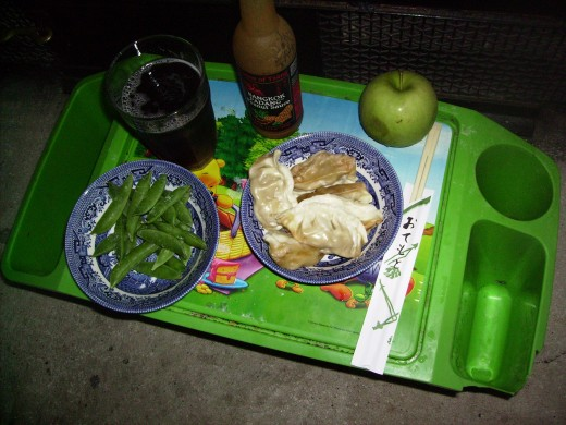 Homemade soda,peanut sauce,  potstickers, green apple, peas in the pod and bamboo chopsticks.