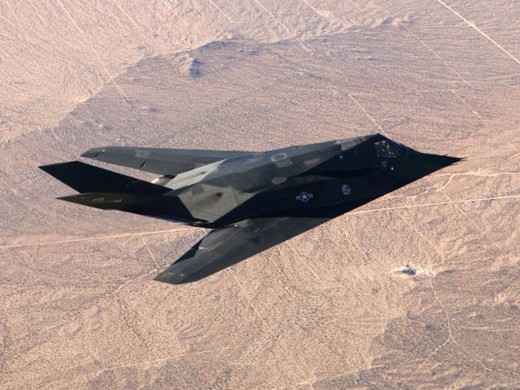 a F-117 Nighthawk stealth fighter seen from above as it flies in daylight over a desert.