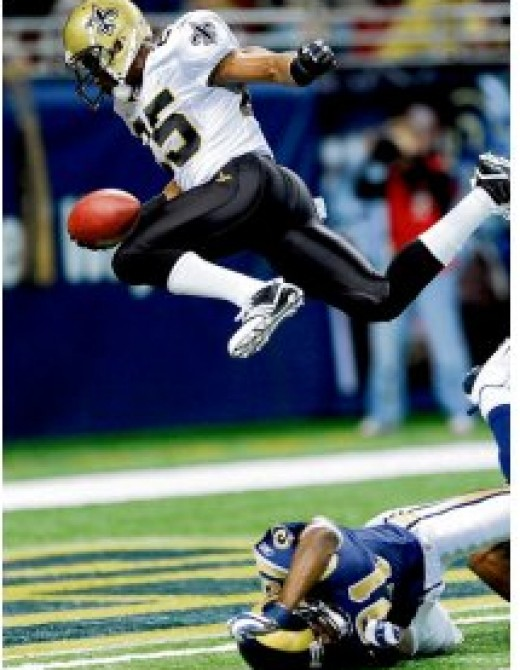 Reggie Bush leaps over Oshiomogho Atogwe to go in for a 3 yd Touchdown Photograph: LG Patterson/AP
