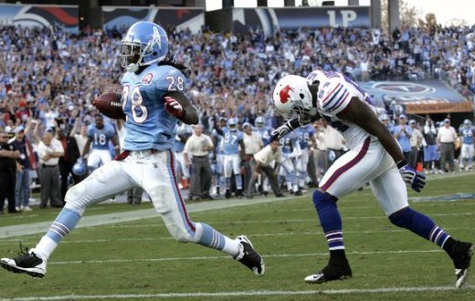 Tennessee Titans #28 Chris Johnson scores a touchdown on a one-yard run ahead of Buffalo Bills linebacker Nic Harris, right, Sunday, Nov. 15, 2009. (AP Photo/Wade Payne)