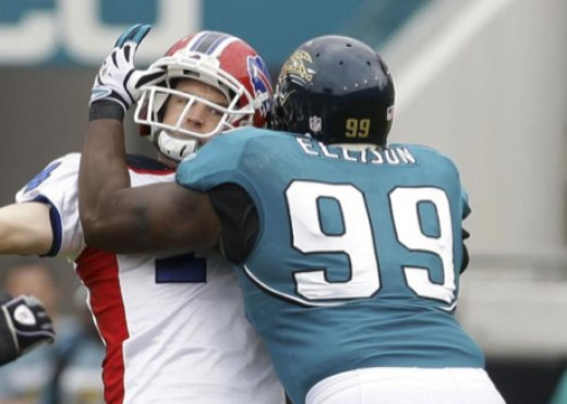 Buffalo Bills quarterback Ryan Fitzpatrick, left, is hit by Jacksonville Jaguars defensive tackle Atiyyah Ellison while throwing a first-quarter pass during an NFL football game, Sunday, Nov. 22, 2009, in Jacksonville, Fla. (AP Photo/Phil Coale)