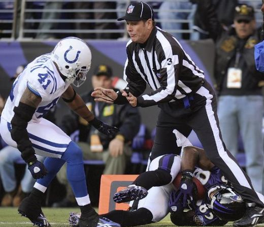 Baltimore Ravens wide receiver Derrick Mason gets tangled up in the feet of field Judge Scott Edwards as Indianapolis Colts safety Antoine Bethea closes in during the fourth quarter of an NFL football game Sunday, Nov. 22, 2009, in Baltimore. (AP Pho