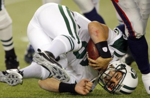 New York Jets quarterback Mark Sanchez (6) lands on the turf after being sacked by New England Patriots linebacker Tully Banta-Cain in the second quarter of an NFL football game in Foxborough, Mass., Sunday Nov. 22, 2009. (AP Photo/Stephan Savoia)