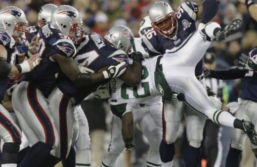 New England Patriots defensive end Ty Warren, left, and linebacker Adalius Thomas (96) and teammates stop New York Jets running back Shonn Greene (23) in the first quarter of an NFL football game in Foxborough, Mass., Sunday Nov. 22, 2009. (AP Photo/