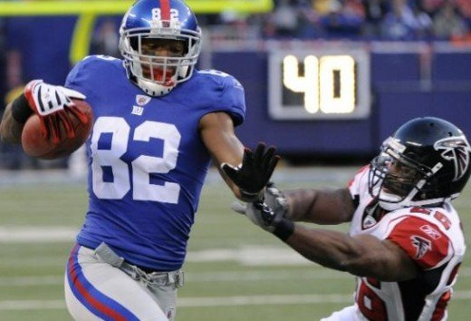 New York Giants wide receiver Mario Manningham (82) is pushed out of bounds by Atlanta Falcons safety Erik Coleman (26) after gaining a first down in overtime of an NFL football game, Sunday, Nov. 22, 2009, in East Rutherford, N.J. (AP Photo/Bill Kos