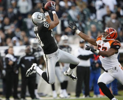 Oakland Raiders wide receiver Chaz Schilens (81) catches the ball in front of Cincinnati Bengals linebacker Dhani Jones (57) in the second quarter of an NFL football game, in Oakland, Sunday, Nov. 22, 2009. (AP Photo/Marcio Jose Sanchez)