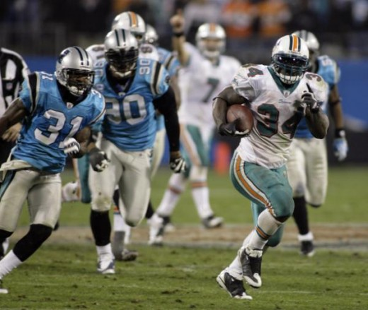Miami Dolphins' Ricky Williams (34) runs past Carolina Panthers' Richard Marshall (31) and Julius Peppers (90) on a 46-yard touchdown in the second half of an NFL football game in Charlotte, N.C., Thursday, Nov. 19, 2009. (AP Photo/Rick Havner)