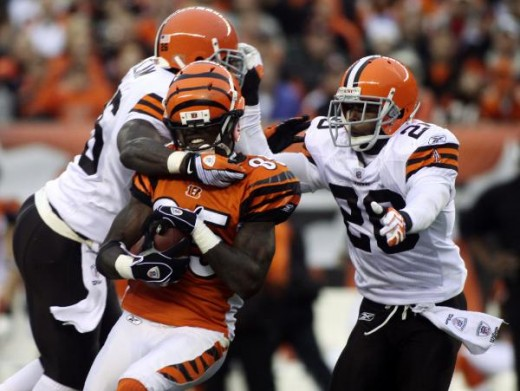 Chad Ochocinco, center, is tackled by Cleveland Browns defenders Abram Elam, left, and Mike Adams during the second half of their NFL football game in Cincinnati, Sunday, Nov. 29, 2009. (AP Photo/Tony Tribble)