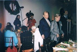An image of Abe and Irene Pollin as they reach their designated spots at a luncheon table.