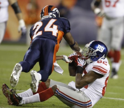 Denver Broncos cornerback Champ Bailey (24) tackles New York Giants wide receiver Mario Manningham (82) during an NFL football game in Denver, Thursday, Nov. 26, 2009. (AP Photo/Darron Cummings)