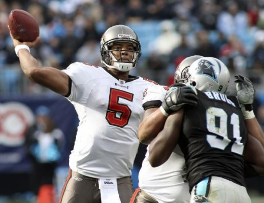 Tampa Bay Buccaneers' Josh Freeman (5) throws a pass under pressure from Carolina Panthers' Everette Brown (91) in the first half of an NFL football game in Charlotte, N.C., Sunday, Dec. 6, 2009. (AP Photo/Rick Havner)