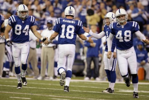 Indianapolis Colts quarterback Peyton Manning (18) is congratulated by tight end Jacob Tamme (84), kicker Pat McAfee, and tight end Justin Snow (48) after the Colts scored a touchdown against the Tennessee Titans in the first quarter of an NFL footba