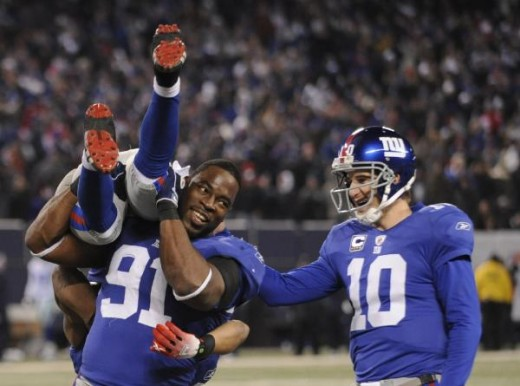 Eli Manning (10) congratulates Domenik Hixon as Hixon is carried off the field by Justin Tuck (91) after Hixon returned a punt for a touchdown in the fourth quarter of their NFL football game against the Dallas Cowboys at Giants Stadium in East Ruthe
