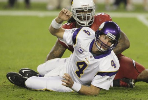 Brett Favre (4) gets up off the ground after being knocked down by Arizona Cardinals' Darnell Dockett in the third quarter during an NFL football game Sunday, Dec. 6, 2009, in Glendale, Ariz. The Cardinals defeated the Vikings 30-17. (AP Photo/Ross D