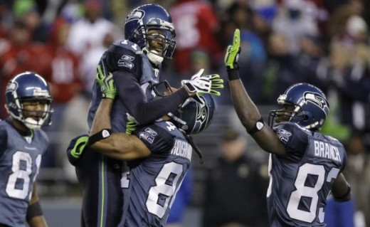 Deon Butler is lifted up by teammate T.J. Houshmandzadeh as Deion Branch share congratulations on Butler's late-game 32-yard catch against the San Francisco 49ers in an NFL football game, Sunday, Dec. 6, 2009, in Seattle. The Seahawks won 20-17. (AP