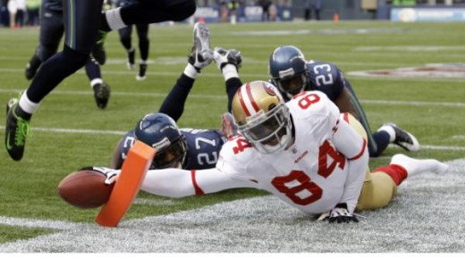 Josh Morgan gets knocked out of bounds on the 1 yard line by Seattle Seahawks? Jordan Babineaux (27) and Seahawks' Marcus Trufant (23) in the first quarter of an NFL football game, Sunday, Dec. 6, 2009, in Seattle. (AP Photo/Ted S. Warren)