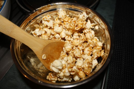 Coating the popcorn with caramel sauce.