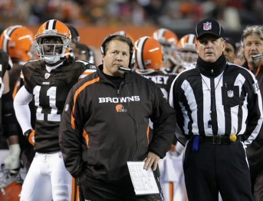 Cleveland Browns coach Eric Mangini, center, watches a replay with wide receiver Mohamed Massaquoi (11) and an official during the second quarter of an NFL football game against the San Diego Chargers, Sunday, Dec. 6, 2009, in Cleveland. The Browns l