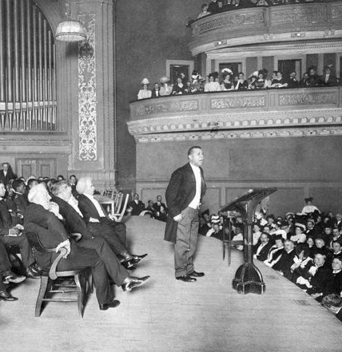 Booker T. Washington speaks at Carnegie Hall at his Tuskegee Institute Silver Anniversary lecture in 1906. Mr. Mark Twain sits just behind him.