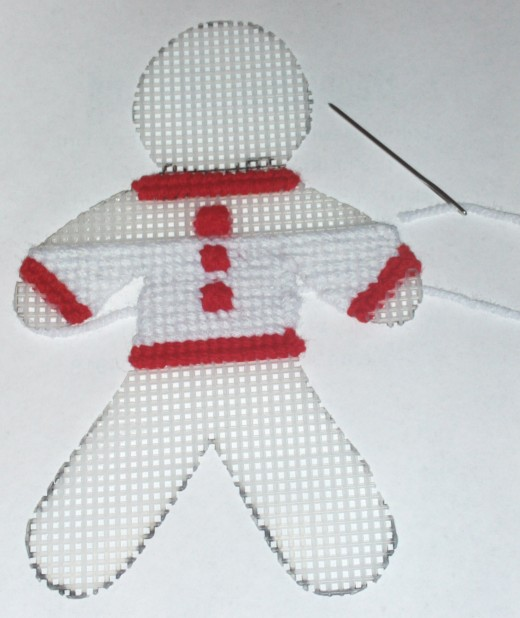 Here I cross stitched on the gingerbread boy's white sweater.  Red and white are festive colors for the holiday season.