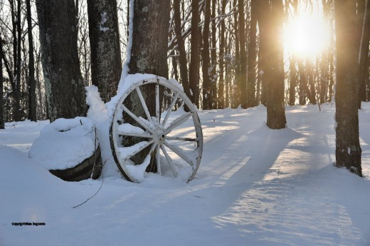 A farm wagon wheel suggests another era when winter meant far more hardships than in modern America.