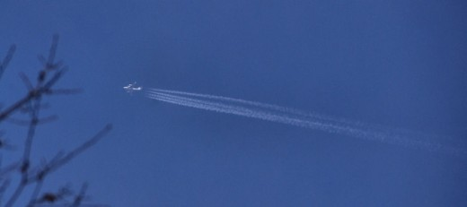 The contrail of a jet cuts across a blue sky.