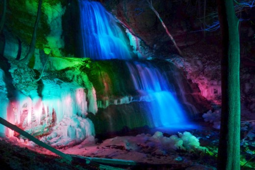 Sherman Falls in Hamilton at night under colored spotlights.