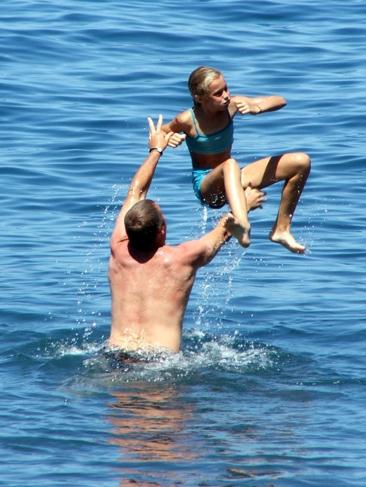 A dad throws his daughter in the ocean. (Photo by Paul de Bruin)