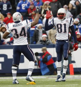 New England Patriots' Randy Moss (81) celebrates a pass interference call with Patriots' Sammy Morris (34) during the first half of the NFL football game in Orchard Park, N.Y., Sunday, Dec. 20, 2009. The Bills were penalized on the play. (AP Photo/ D
