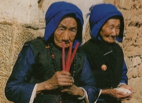 Candles and rice are part of the daily ritual for these Bai women. Yunnan Province, China.