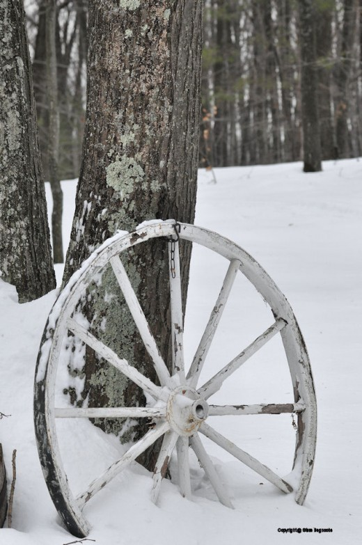 Rust shows more clearly on the old wagon wheel in winter when snow blankets the yard.