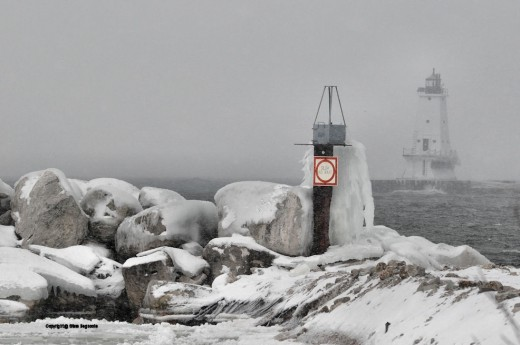 """Ice coats the lakeward facing side of a """"no wake"""" sign at a Lake Michigan boat launch in Ludington. The Ludington North Breakwater Light hulks in the background."""