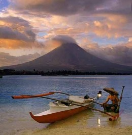 The solace and idyllic view of the Mayon Volcano. A traditional boat here provides a lovely and artistic scene.