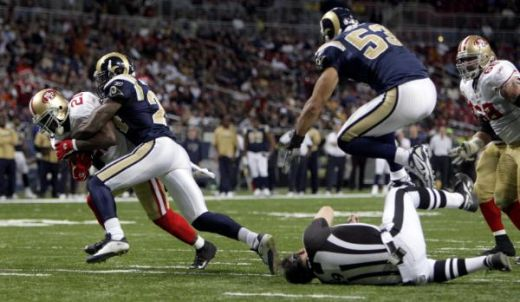 St. Louis Rams linebacker Paris Lenon (53) leaps over umpire Steve Wilson, bottom right, after he was knocked down by San Francisco 49ers running back Frank Gore, left, as Gore runs for a short gain before being brought down by St. Louis Rams cornerb