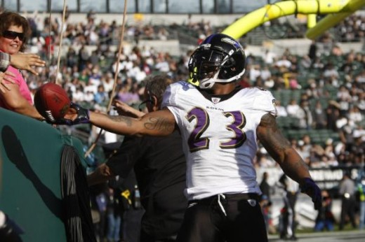 Baltimore Ravens running back Willis McGahee (23) hands the ball to a fan after scoring a touchdown in the first quarter of an NFL football game in Oakland, Calif., Sunday, Jan. 3, 2010. (AP Photo/Paul Sakuma)