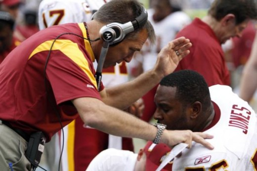 Washington Redskins offensive tackle Levi Jones is consoled by coach Jim Zorn during the fourth quarter of the Redskins' 23-20 loss to the San Diego Chargers in an NFL football game Sunday, Jan. 3, 2010, in San Diego. (AP Photo/Chris Park)