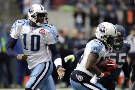 Tennessee Titans quarterback Vince Young, left, hands off to teammate Chris Johnson, right, in the first quarter of an NFL football game against the Seattle Seahawks, Sunday, Jan. 3, 2010, in Seattle. (AP Photo/Elaine Thompson)