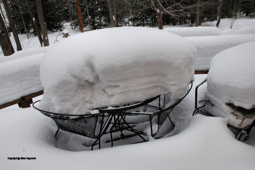 Snow is piled high on the table on the deck overlooking the backyard.