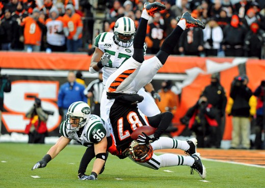 Bengals receiver Andre Caldwell (87) is upended by New York Jets safety Jim Leonhard (36) in the first half of the game. Credits: Antonelli/News