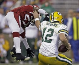 Green Bay Packers' Aaron Rodgers (12) evades the rush of Arizona Cardinals' Michael Adams (27) during the first half of an NFL wild-card playoff football game Sunday, Jan. 10, 2010, in Glendale, Ariz. (AP Photo/Paul Connors)